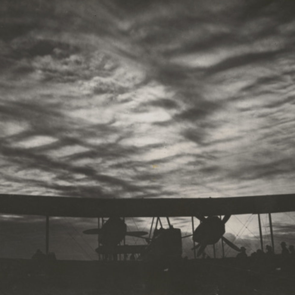 Image: Black and White photograph showing biplane with clouded sunset. Shadows of men gathered by the right wing